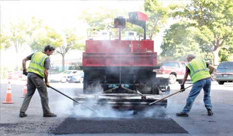 2 asphalt workers smoothing out heated asphalt