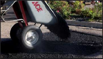Worker dumping wheelbarrow full of asphalt